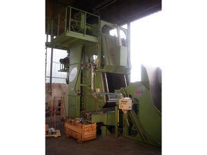 Tumble blast machine with manganese steel belt